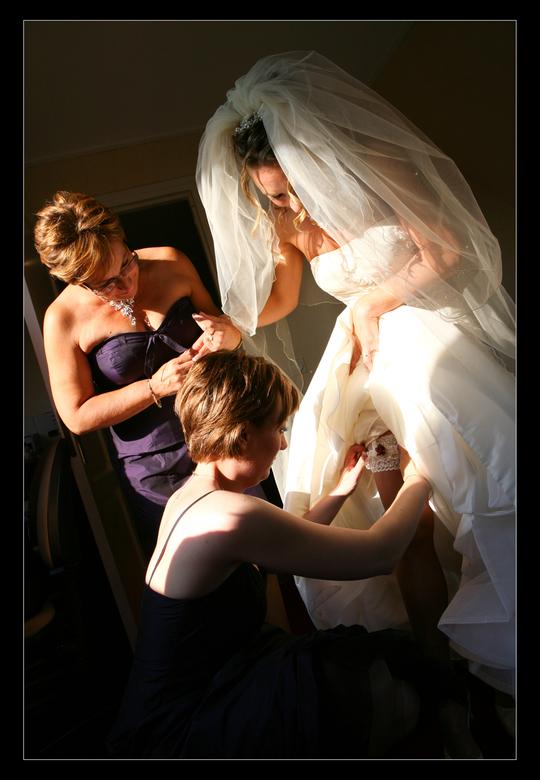 bride-5 - de bruid moest even geholpen worden met het omdoen van de kouseband.<br /> Deze was ze bijna in alle drukte vergeten. Leverde mij een mooi
