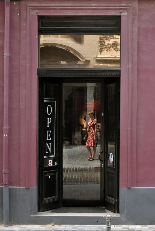 Back in Time - Gespot op straat in Leuven achter de glazen deur stond een verlicht beeld. Op straat een passant<br /> Een ontmoeting tussen het heden