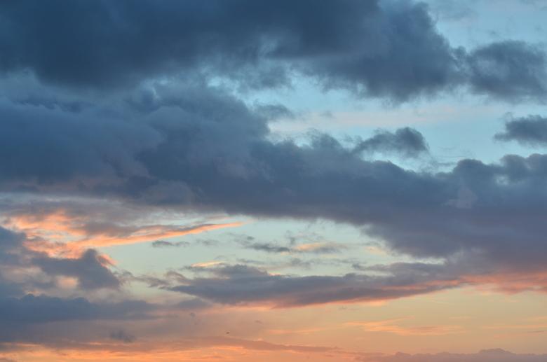 Zon weg, regen komt - Tijdens een prachtige zonsondergang dringen de donkere regenwolken zich op.