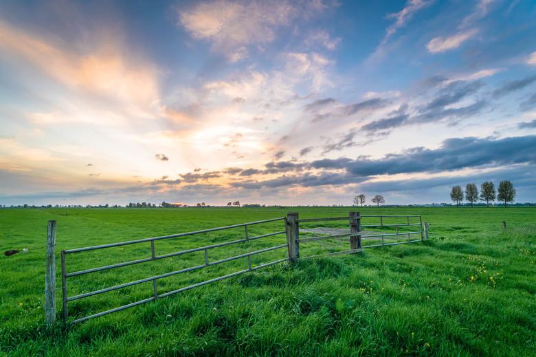 Zonsondergang boven een hek.