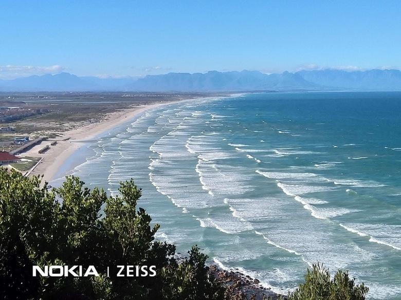 1AD003A4-98EE-49DD-837E-F28DB1CB3A8C - Deze foto  van het strand van Muizenberg ( Zuid - Afrika) is genomen vanaf een hoger gelegen bergweg. De golven