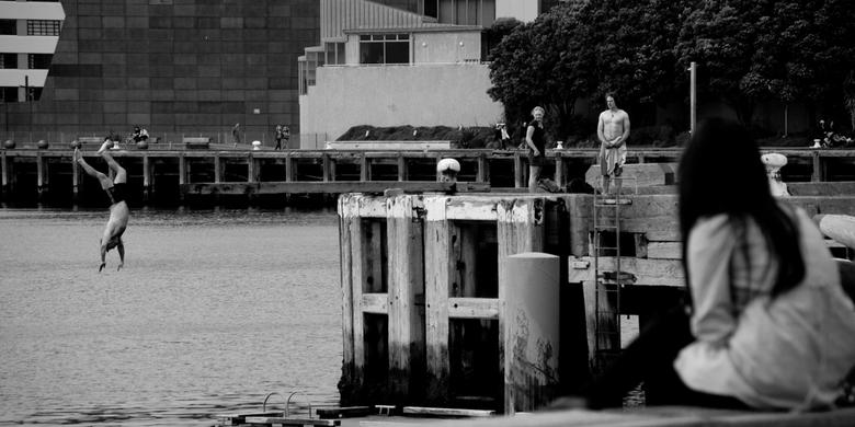 Weekend in Wellington - Jongeren vermaken zichzelf en elkaar aan de boulevard in de haven van downtown Wellington, Nieuw Zeeland.