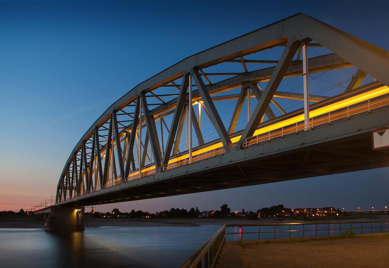 Spoorbrug Nijmegen - Nachtopname van de spoorbrug over rivier de Waal in Nijmegen. Op de spoorbrug is een rijdende sneltrein te zien.
