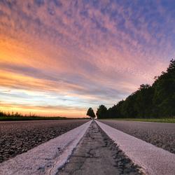 Zonsondergang midden op de weg