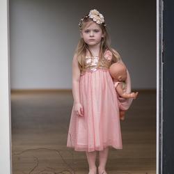 meisje in deuropening met pop