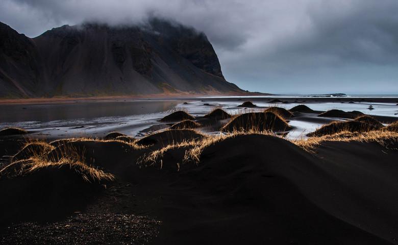 Stokksnes duinlandschap - De zwarte zand/lava duinen van Stokksnes met uitzicht op Vestrahorn, omgeven door bewolking en mist.