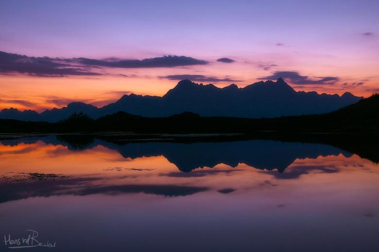 Miroir - Na dat de zon onder de bergrand was verdwenen werd de lucht mooi paars en zacht van kleur. Het spiegelgladde meer verdubbelde het geheel <img