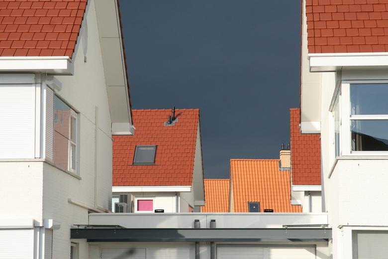 Daken - De daken van de nieuwgebouwde huizen in onze wijk, met op de achtergrond een dreigende onweerslucht.