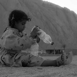 kind met water in de woestijn