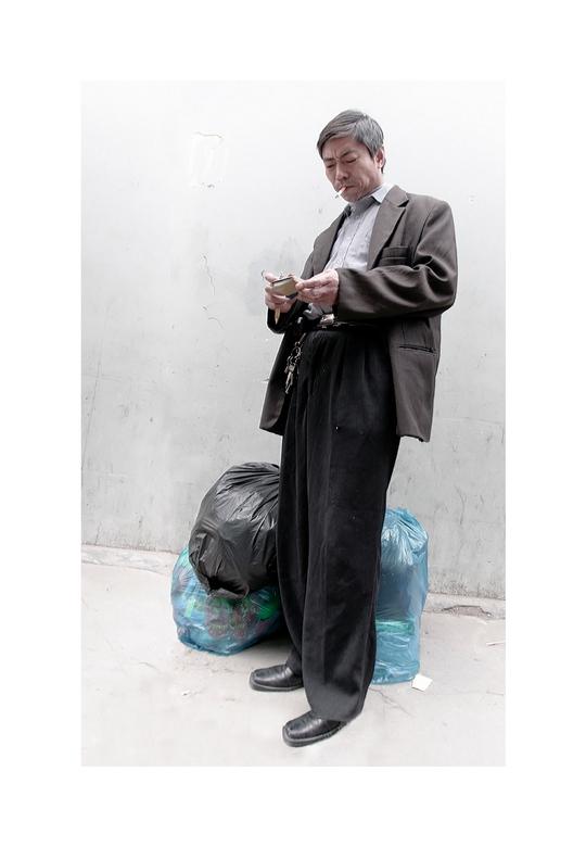Shanghai 6 - Deze handelaar staat met zijn handelswaar notities te maken in een klein boekje.<br /> <br /> Nr 6 uit de serie.<br /> <br /> Groet,<