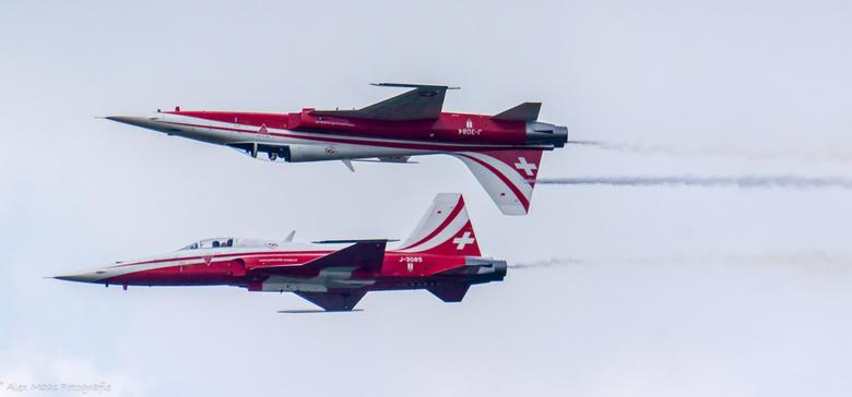 Patrouille de Suisse - 2 Zwitserse gevechtsvliegtuigen die boven elkaar vliegen, waarvan er 1 ook ondersteboven vliegt