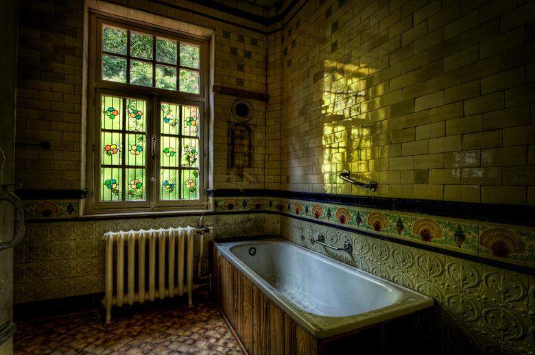 Badkamer Reflectie - Door de glas in lood ramen komt er een spookachtige groene gloed de badkamer van deze verlaten villa binnen.