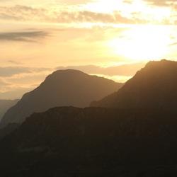 De zon verdwijnt achter de bergen