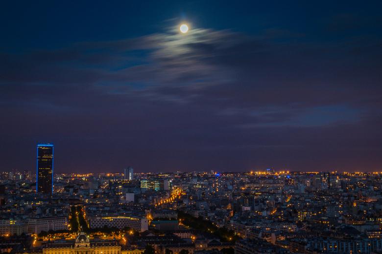 Nachtfoto Parijs - Een nachtfoto genomen vanaf de Eiffeltoren met op de achtergrond een volle maan