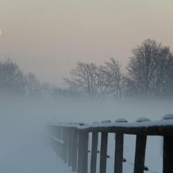 Besneeuwd hek met maan en nevel