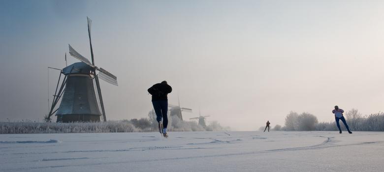 schaatsers bij Kinderdijk - Een foto voor de fotowedstrijd. De eerste schaatsers bij de molens van Kinderdijk.