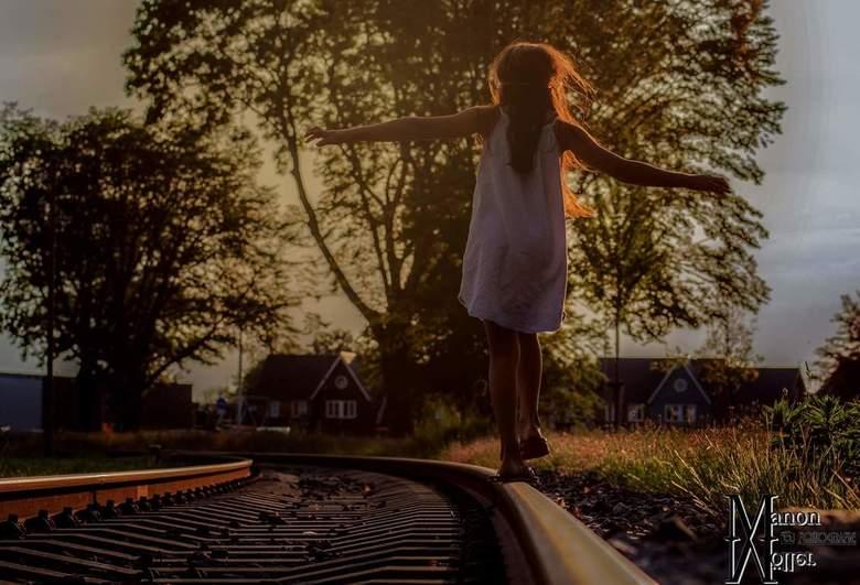 Spoormeisje - Meisje op verlaten spoor bij zonsondergang.