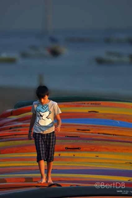"""Kanojongen - Een jongen speelt bij valavond op de kanos die op het strand van Bénodet in Bretagne liggen te rusten na een gedane dagtaak <img  src=""""/i"""