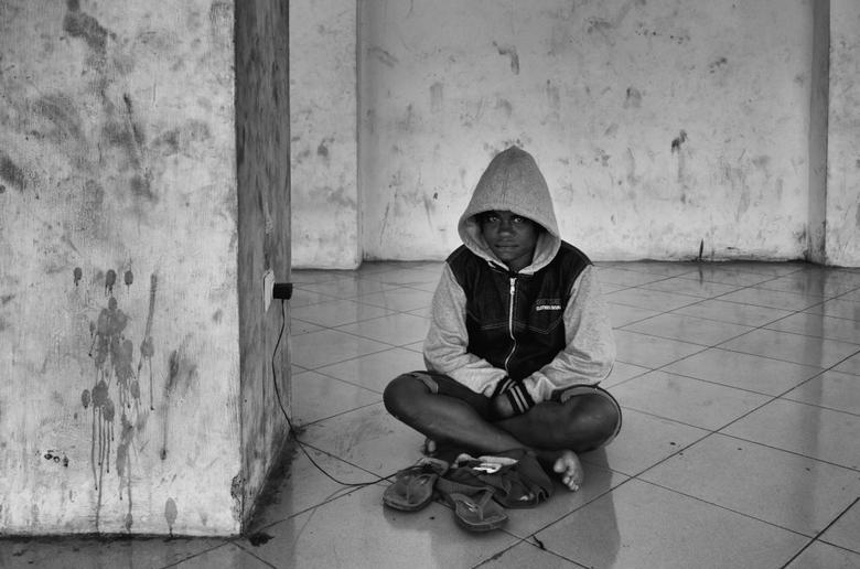 Even opladen - Een jongen laadt zijn telefoontje op in een verlaten mall in Papua.
