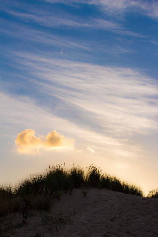 wolk in duin  - Een wolk mooi belicht door de ondergaande zon in Oostkapelle Zeeland. Duin wazig en donker op de voor grond.