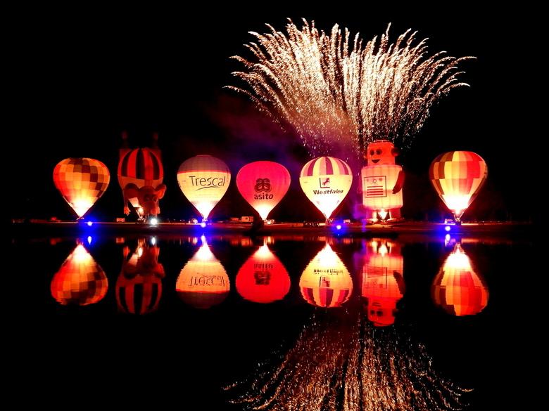 Twente ballooning - nightglow, heteluchtballonnen langs de waterkant opgesteld die beurtelings op het ritme van muziek worden gefakkeld. Tegelijkertij