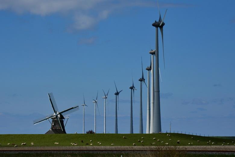 Molens - Molens, oud en nieuw. <br /> In het Eemshavengebied, in noord-Groningen staan tientallen high-tech windturbines. Deze rij sluit prachtig aan