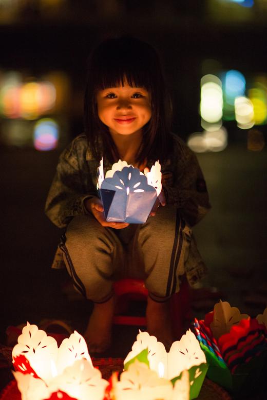 Kaarsreflectie - Dit meisje verkocht lampionnetjes voor het volle maan festival.