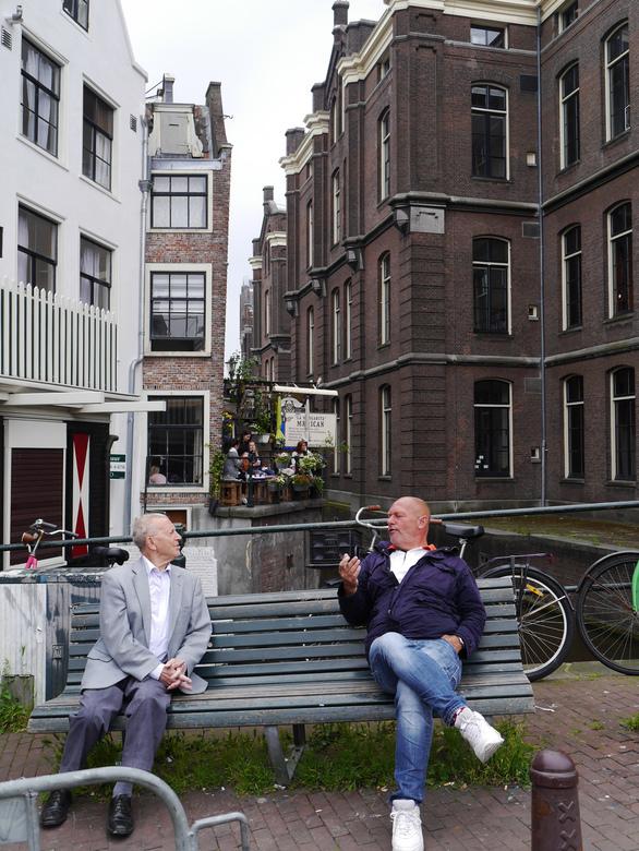 Een schuin gesprek - Twee heren op een bankje in Amsterdam die in gesprek zijn geraakt