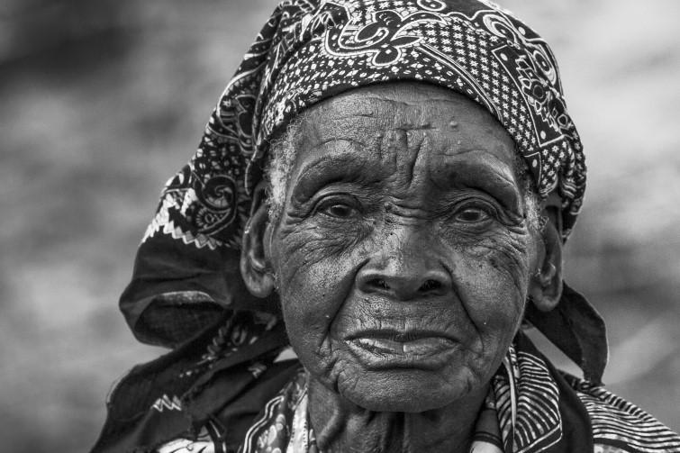 A Story - De oudste vrouw van een wijk, welke achter een fruitkraampje zat, staat op om de (waarschijnlijk zeldzame) blanken in de wijk te bekijken en