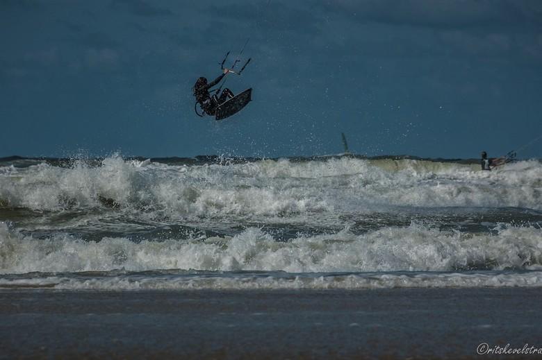 Kitsurfer Egmond aan Zee. - Erg hoge golven en harde wind bij Egmond aan Zee. Deze surfster gebruikte alle twee om zo hoog boven de golven te zweven.