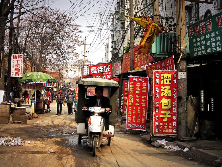 Een straat in Kaifeng - Veel van de straatjes in het provincie stadje Kaifeng zijn onverhard. Ondanks de kuilen, lopende mensen en loslopende dieren s