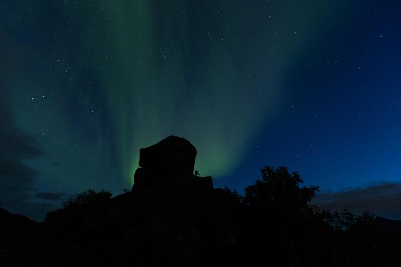 Noorderlicht achter een hoofd op de Lofoten -