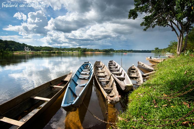 """Nieuw Lombé Haven - Het asfalt naar """"de stad"""" (Paramaribo) houdt aan de overkant van de Surinamerivier bij Klaaskreek op. Korjalen als deze zijn hier"""