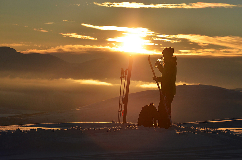 Toptur - Deze skister neemt een slokje water voor ze begint aan haar afdaling van Rødtinden in de zonsondergang. Genomen nabij Tromsø, Noorwegen.