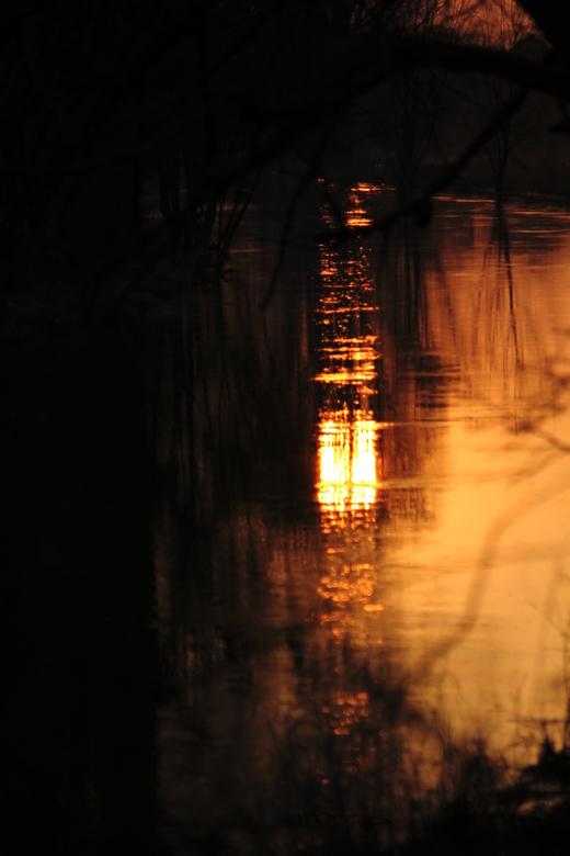 Spiegel van de ondergaande zon - Weerspiegeling van de ondergaande zon in een beekje bij Goch (D)