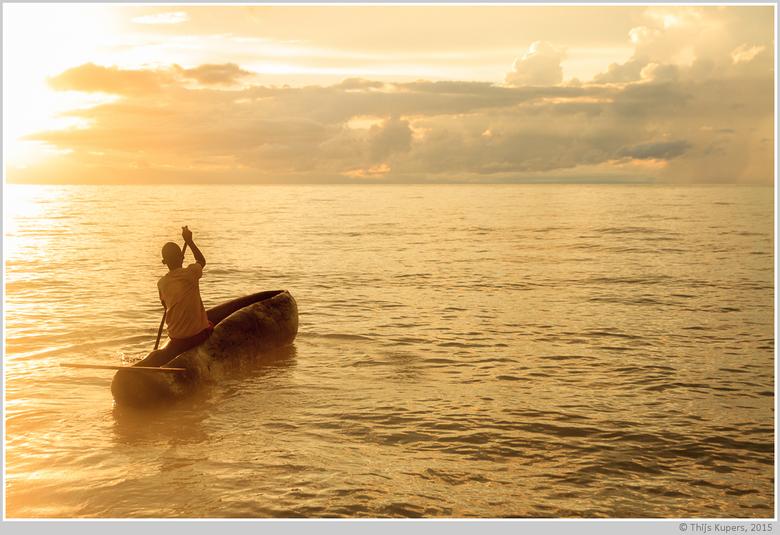 Farewell - Een jonge Malawiër vaart &#039;s ochtends uit op het Meer van Malawi om te gaan vissen.<br /> <br /> Hij was &#039;s ochtends net na zons