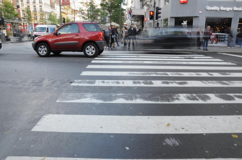Straatrace? - Een rijdende en een stilstaande auto op een kruispunt in Antwerpen.