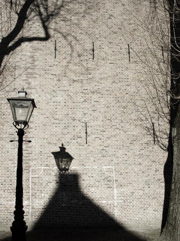 Straatlantaarnschaduw - De schaduw van een straatlantaarn op een grote muur in de felle zon