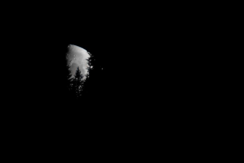 Zie de maan schijnt door de bomen... - Niet alledaagse situatie, maar de maan trekt achter een tegenovergelegen berg langs, mat dit als resultaat. Wel