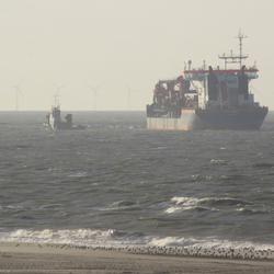 Zandschip loost via lange leiding naar het strand.