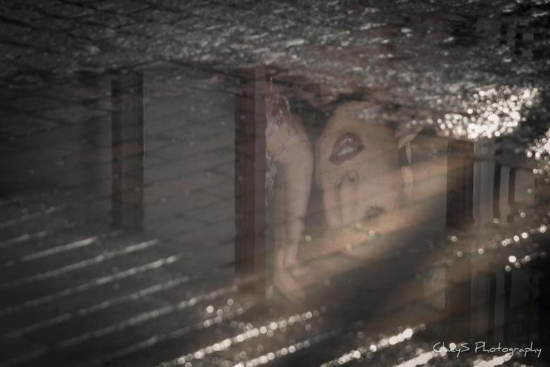 Lady Reflection - Weerspiegeling van een winkel façade in een plas water