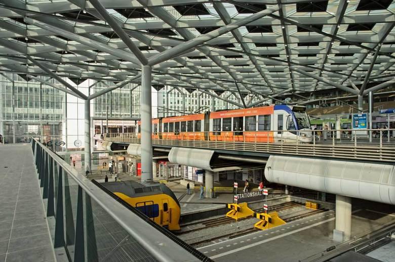 Tram en trein op Den Haag CS - Een intercity staat aan het perron van Den Haag CS met daarboven een tram onder de nieuwe overkapping van de openbaar v