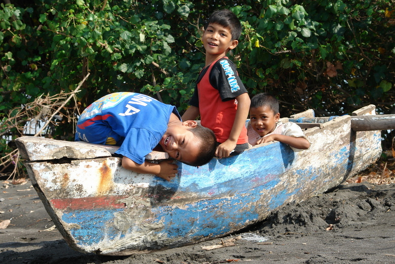 spelen - Balinese kinderen, hier bij hun woning, aan het strand, vermaken zich met het oude kapotte vissersbootje van hun vader.