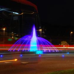 Verlichte fontein met passerende bus Hermes