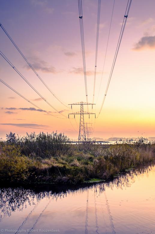 Licht in de polder - Polder Woerden tijdens zonsondergang. Dmv van elektriciteit/hoogspanning diepte in foto ingebracht..