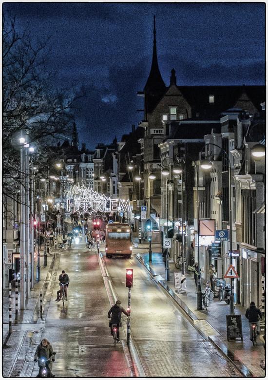 Haarlem gaat naar huis - Foto genomen vanaf balustrade onderdoorgang Station Haarlem in de richting van de stad. Mooie reflecties door natte wegdek.
