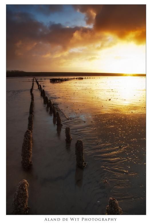 Sunset over a shipwreck - De Waddenzee, paaltje, scheepswrak en een mooie zonsondergang. Gemaakt bij Wierum aan het Wad Friesland.