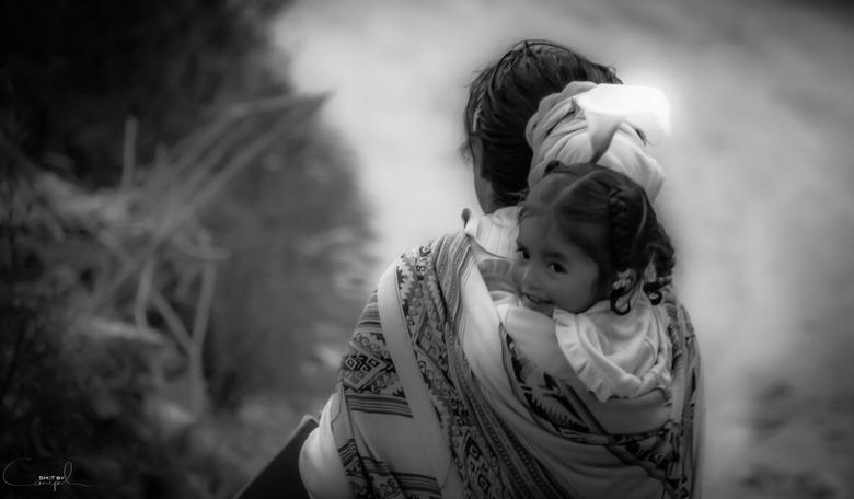 """Little smile - schattig meisje op de rug van de moeder... lachend achteruit kijkend <img  src=""""/images/smileys/smile.png""""/> schattig"""