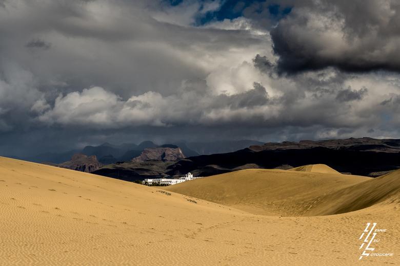 Stulpje in de woestijn - Hotel aan de duinen in Playa de Ingles met slecht weer in de bergen en vol op zon aan de kustlijn.