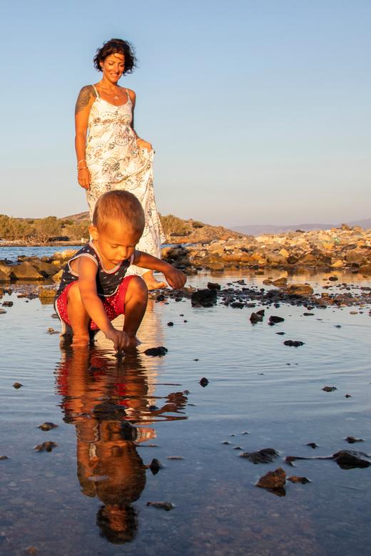 Moeder en zoon - Een moeder kijkt liefdevol naar haar zoontje die in het water speelt.